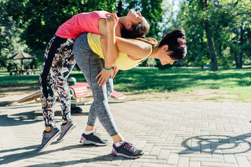 Woman stretching with help of a personal trainer