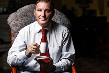 Serious middle-aged businessman with coffee cup