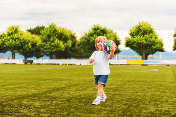 Adorable little 3 year old boy playing soccer on the stadium