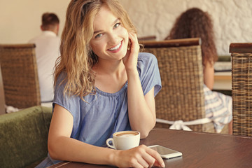 Beautiful girl with cup of coffee in cafe