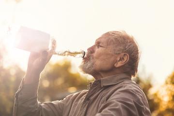 Пенсионер пьет воду на проироде