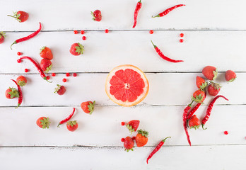 Red fruits and vegetables on a white on a wooden background