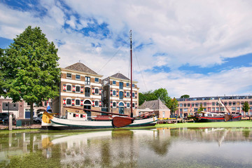 Acrylic Prints Channel Ancient renovated mansion with a white moored boat mirrored in a canal. .