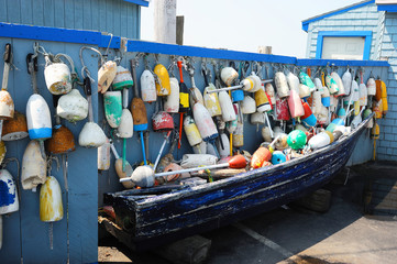 boat and old colorful fishing buoy hanging on the wall for decoration