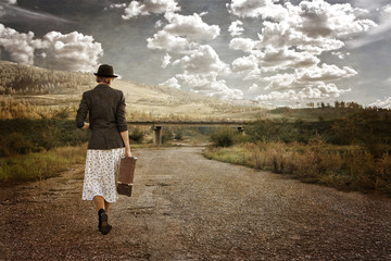 Women with vintage suitcase at old road. Photo in retro style