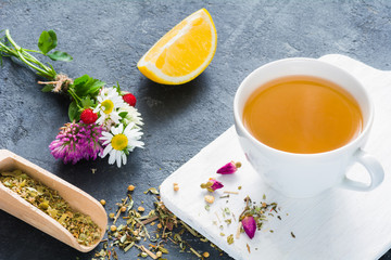 Cup of herbal green tea, lemon wedge, dry herbal tea, rose buds and bouquet of flowers. Concept of antioxidant beverage, healthy lifestyle, dieting, well-being.