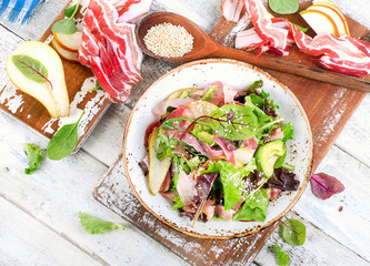 Fresh mixed salad with bacon on a white wooden table.