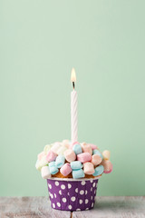 Birthday vanilla cupcake with colorful marshmallows and candle on mint green background