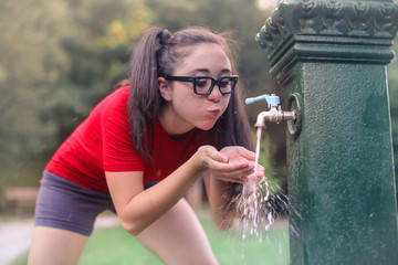Thirsty teenager drinking water at the park