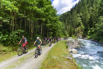 eine Gruppe Mountainbiker fährt an einem Wildbach in den Alpen entlang aufwärts