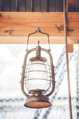 Vintage western lantern hanging on a wooden plank