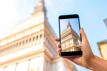 Holding a smart phone with photo of Mole Antonelliana cinema museum building in Turin city in Piedmont region in Italy