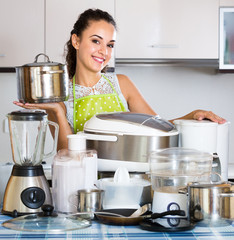 Positive housewife with kitchenware in kitchen