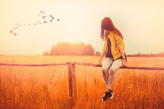 Young girl woman sitting on a fence and looking the summer orange sun landscape in the nature with birds