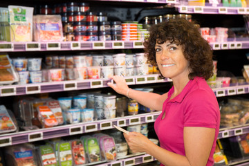 Woman in the supermarket, customer in front of product