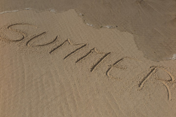"""summer"" handwritten on sand, summer background, sea and sand background"