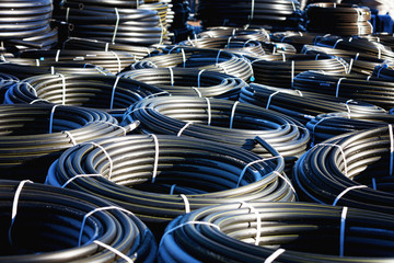 stacks of black pvc plastic pipe outdoors with selective focus