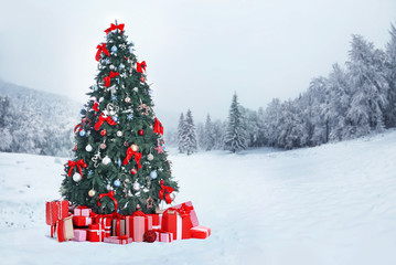 Decorated Christmas tree with gifts on nature background. Christmas holiday concept.