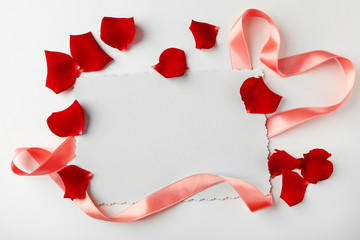 Flower petals with silk ribbon and card isolated on white
