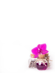 Pink orchid and group glass bottles on a white background. Spa concept. Cosmetic bottles. Ecological natural cosmetics. Copy space.