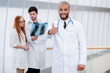 Portrait of a successful doctor showing thumb up. Three confiden