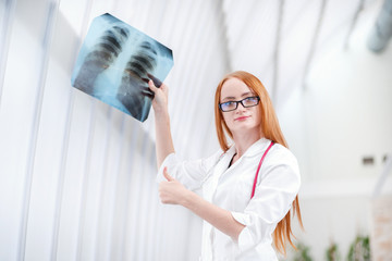 Female doctor examining an x-ray to work patient and showing thu