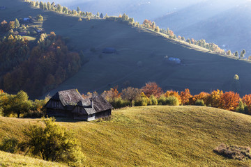 Autumn Landscape with a wooden house on the slopes of the mountains. Beautiful light and sun rays