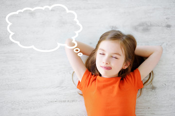 Little girl lying on white wooden floor with a speech bubble above her head