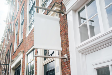 Photo blank signboard on the city street. White square signboard on the brick wall. Mock up.