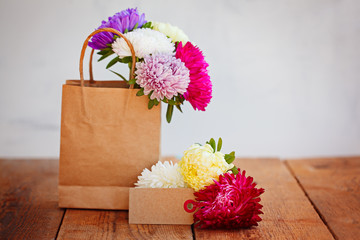 Bouquet of colorful asters in paper bag with empty greeting card