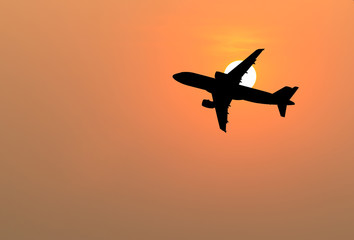 Silhouette of big airplane on beautiful orange sunset background, fast aerial transport, traveling and voyage concept