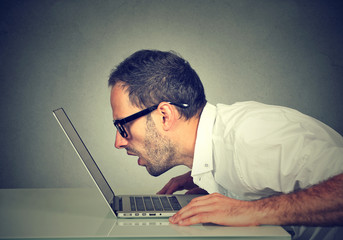 Side profile man staring closely intensely at laptop screen