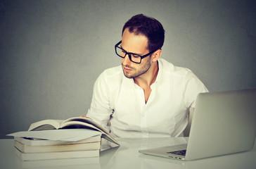 young business man working with laptop reading books