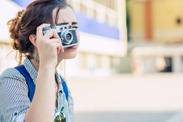 happy young tourist woman or teenage girl with film camera