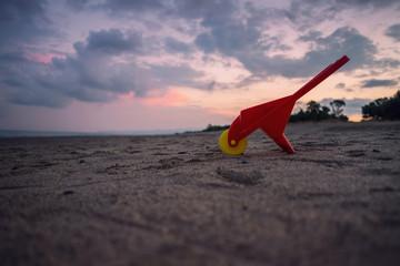 Carriola Rossa giocattolo isolata sulla spiaggia durante un tramonto
