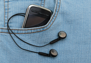 Player with headphones in the pocket of jeans