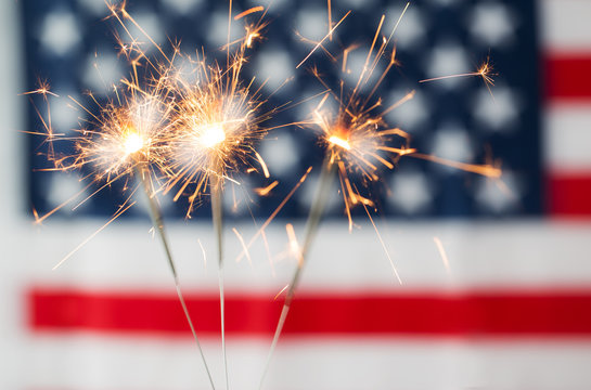 close up of sparklers burning over american flag