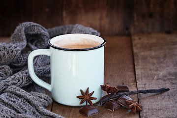 Enamel cup of hot cocoa or coffee for Christmas with chocolate bars, vanilla pod, spices and gray scarf against a rustic background. Shallow depth of field with selective focus on drink.