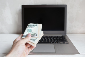 Bunch of hundred dollar bills and laptop. Hand put american money banknotes to computer screen in giving gesture. Online shopping, bets, casino concept