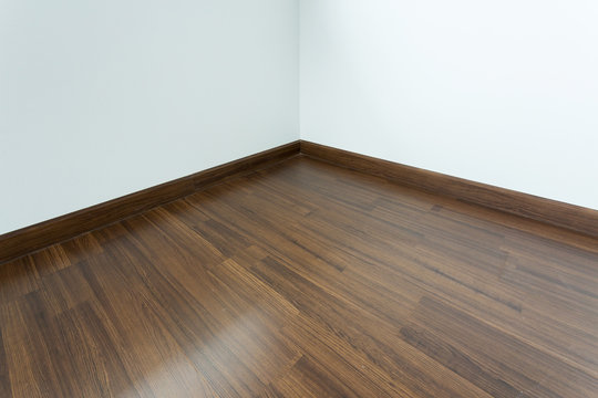 empty room interior, brown wood laminate floor and white mortar