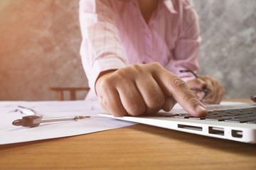 Close up photo of woman using laptop to draw scheme