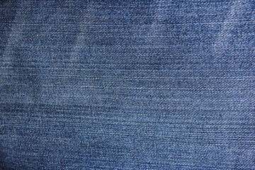 Jeans texture dark background close up blue and white denim natural pattern fabric clothes with diagonal lines and stitches
