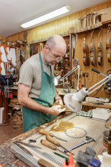 Violin maker working on new instrument in his workshop