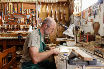 Instrument maker looking at neck of new violin he is working on
