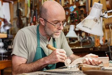 Violin maker in his workshop carving on neck of a new instrument