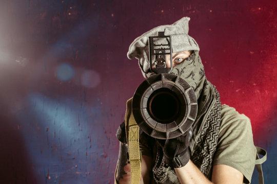 Portrait of man aiming through bazooka gun