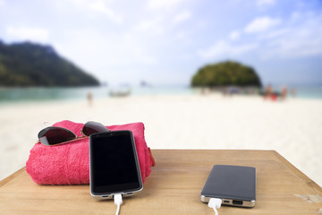Red tower, sun glasses, mobile charging with power bank over woo
