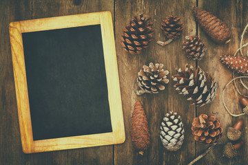 Top view of pine cones and blank blackboard