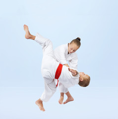 Boy and girl in judogi are training throws