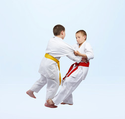 Boys in judogi are training grip for throw
